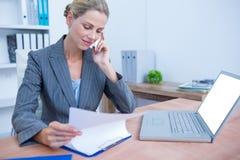 Femme d'affaires assez blonde téléphonant et à l'aide de son ordinateur portable Photo stock