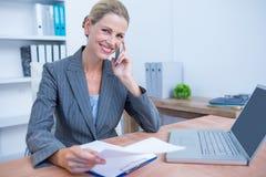 Femme d'affaires assez blonde téléphonant et à l'aide de son ordinateur portable Photographie stock libre de droits