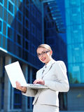 Femme d'affaires assez jeune dans le blanc utilisant l'ordinateur portable image libre de droits
