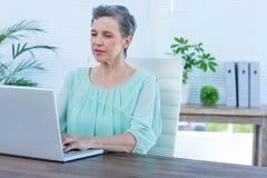 Femme d'affaires attentive travaillant sur son ordinateur portable Photographie stock libre de droits