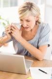 Femme d'affaires attentive travaillant sur un ordinateur portable Photo stock