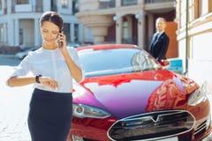 Femme d'affaires attirante agréable regardant sa montre Image libre de droits