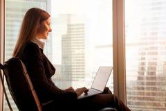 Femme d'affaires attirante appréciant le coucher du soleil, détendant dans le cha de bureau Image libre de droits