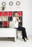Femme d'affaires attirante au téléphone dans le bureau blanc photographie stock