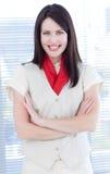 Femme d'affaires attirante avec le sourire plié de bras Image stock