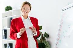 femme d'affaires attirante dans la position rouge de veste près du flipchart photo libre de droits