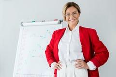 femme d'affaires attirante dans la position rouge de veste près du flipchart dans le bureau et le regard photographie stock