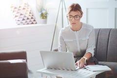 Femme d'affaires attirante de fonctionnement dur se concentrant sur son travail Image stock