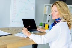 femme d'affaires attirante de sourire s'asseyant à la table avec l'ordinateur portable photo libre de droits