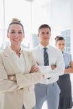 Femme d'affaires attirante de sourire se tenant avec des bras pliés Image stock