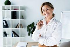 femme d'affaires attirante de sourire tenant des verres et regardant loin images libres de droits