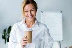femme d'affaires attirante de sourire tenant la tasse de café jetable dans le bureau et le regard images stock