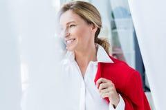 femme d'affaires attirante de sourire tenant la veste rouge et parlant par le smartphone image stock