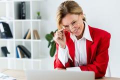 femme d'affaires attirante de sourire touchant des verres et regarder l'ordinateur portable photographie stock libre de droits