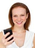 Femme d'affaires attirante envoyant un texte photo stock