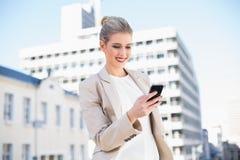 Femme d'affaires attirante gaie envoyant un message textuel photos stock