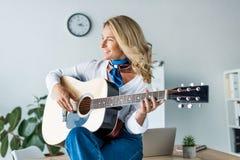 femme d'affaires attirante heureuse jouant la guitare acoustique image stock