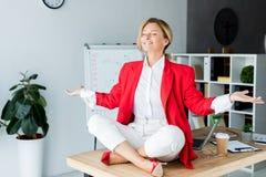 femme d'affaires attirante heureuse méditant dans la pose de lotus sur la table photographie stock