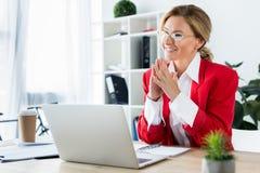 femme d'affaires attirante heureuse s'asseyant à la table avec l'ordinateur portable photographie stock