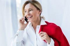 femme d'affaires attirante heureuse tenant la veste rouge et parlant par le smartphone photographie stock libre de droits