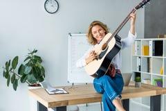 femme d'affaires attirante jouant la guitare acoustique photos stock