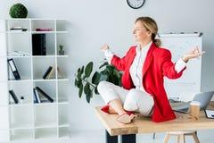 femme d'affaires attirante méditant dans la pose de lotus sur la table image libre de droits