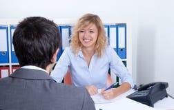 Femme d'affaires attirante parlant avec un client Photographie stock libre de droits