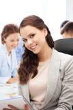 Femme d'affaires attirante prenant des notes dans le bureau photos stock