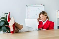 femme d'affaires attirante regardant l'ordinateur portable avec des jambes sur la table photo stock