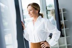 femme d'affaires attirante regardant la fenêtre photo stock
