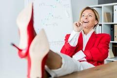 femme d'affaires attirante riant et s'asseyant avec des jambes sur la table photos libres de droits