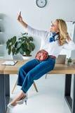 femme d'affaires attirante s'asseyant sur la table dans le bureau et prenant le selfie photographie stock