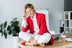 femme d'affaires attirante s'asseyant sur la table et regardant la caméra photographie stock libre de droits