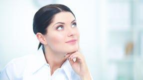 Femme d'affaires attirante s'asseyant sur le bureau dans le bureau Photo stock