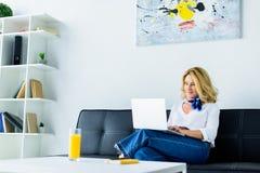 femme d'affaires attirante s'asseyant sur le sofa dans le bureau et le travail photos libres de droits