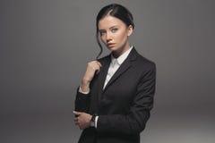 Femme d'affaires attirante sûre portant le costume noir et regardant l'appareil-photo Images libres de droits