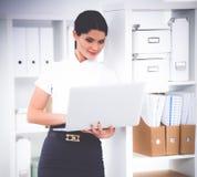 Femme d'affaires attirante se tenant dans le bureau avec l'ordinateur portable Photo stock