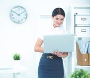 Femme d'affaires attirante se tenant dans le bureau avec l'ordinateur portable Photos stock
