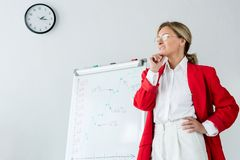 femme d'affaires attirante songeuse dans la position rouge de veste près du flipchart images libres de droits