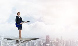 Femme d'affaires attirante sur le plateau en métal jouant la guitare électrique sur le fond de paysage urbain Photos stock