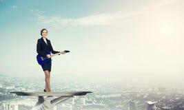 Femme d'affaires attirante sur le plateau en métal jouant la guitare électrique sur le fond de paysage urbain Photo libre de droits