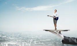Femme d'affaires attirante sur le plateau en métal jouant la guitare électrique sur le fond de paysage urbain Images libres de droits