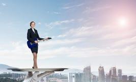 Femme d'affaires attirante sur le plateau en métal jouant la guitare électrique sur le fond de paysage urbain Image stock