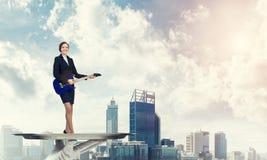 Femme d'affaires attirante sur le plateau en métal jouant la guitare électrique sur le fond de paysage urbain Images stock