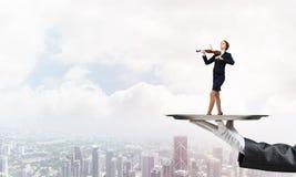Femme d'affaires attirante sur le plateau en métal jouant le fond de paysage urbain d'aginst de violon Images libres de droits
