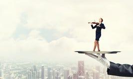 Femme d'affaires attirante sur le plateau en métal jouant le fond de paysage urbain d'aginst de violon Images stock