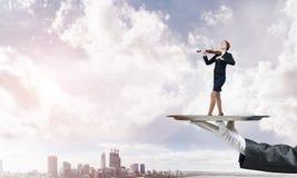 Femme d'affaires attirante sur le plateau en métal jouant le fond de paysage urbain d'aginst de violon Photos libres de droits