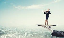 Femme d'affaires attirante sur le plateau en métal jouant le fond de paysage urbain d'aginst de violon Photo stock