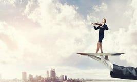 Femme d'affaires attirante sur le plateau en métal jouant le fond de paysage urbain d'aginst de violon Photos stock