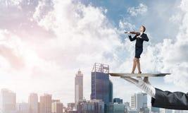 Femme d'affaires attirante sur le plateau en métal jouant le fond de paysage urbain d'aginst de violon Photographie stock